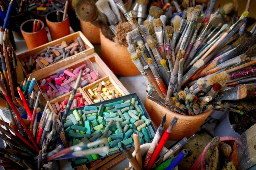 pastels et pinceaux dans des pots.