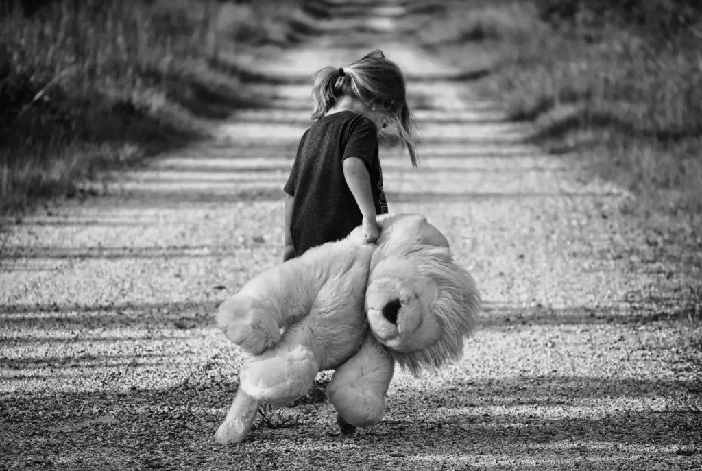 petite fille tenant un peluche sur un chemin