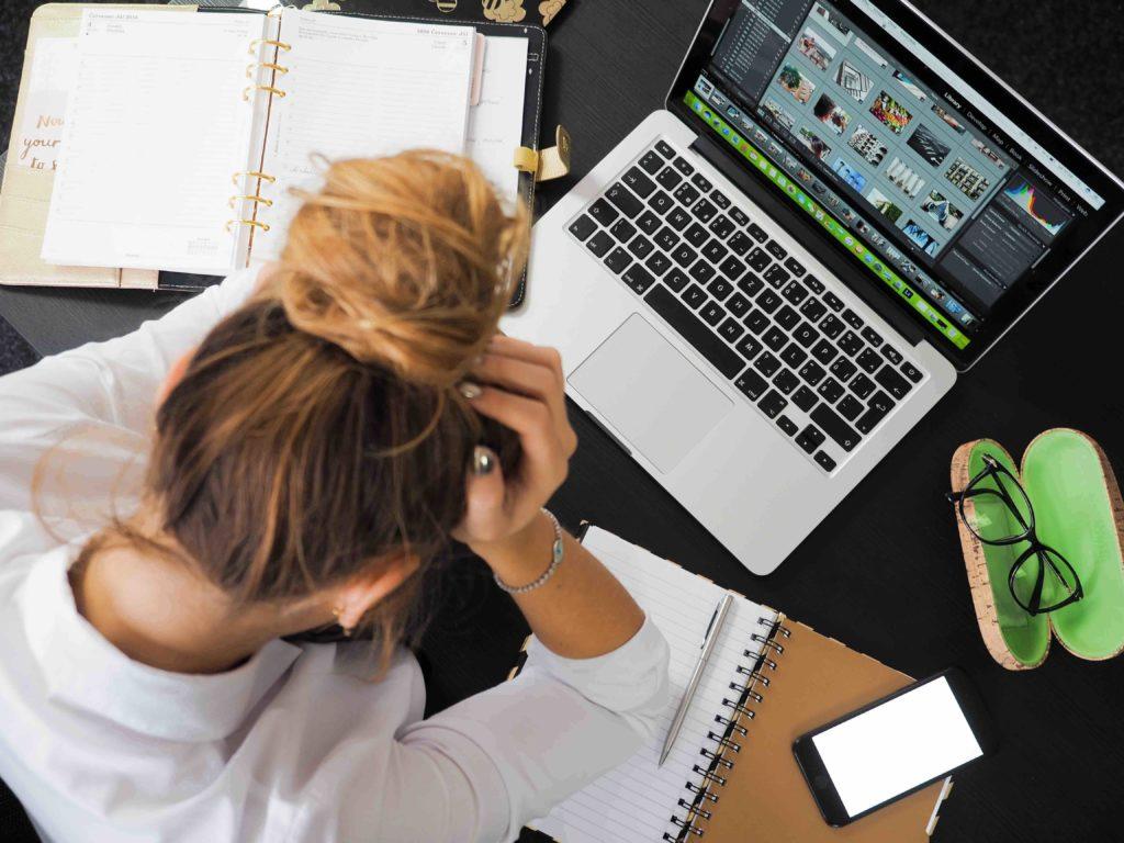 femme se tenant les cheveux devant son ordinateur