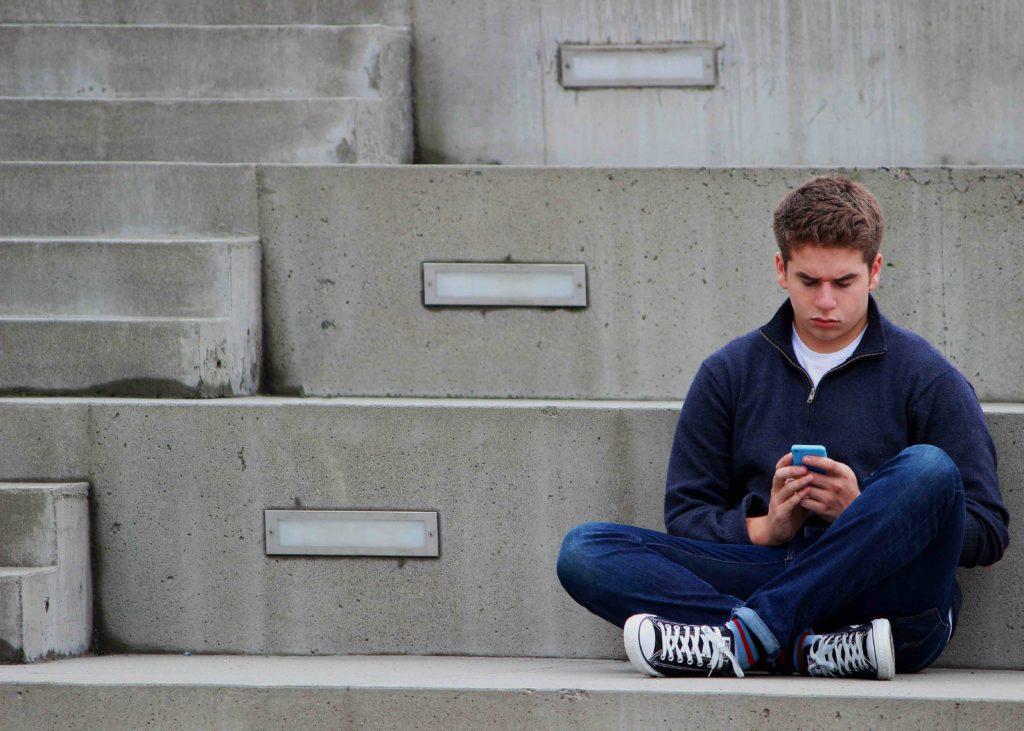 garçon seul regardant son portable